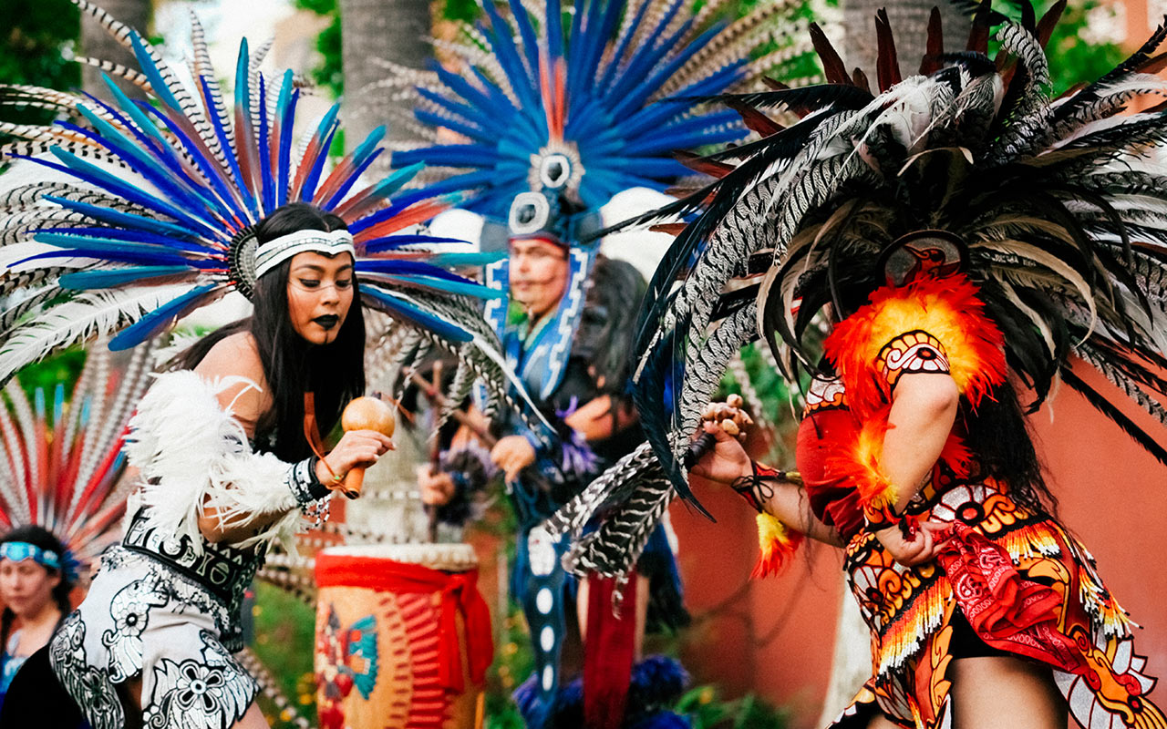 Aztec dancers performing around palm trees in the garden at the Mexican Heritage Plaza