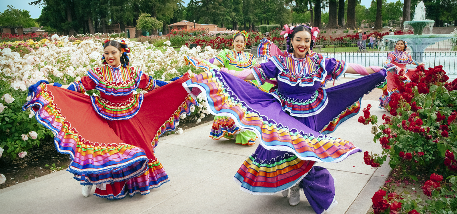 Dancers in tradition Mexican dresses dancing among thousands of rose buds in the Municipal Rose Garden.