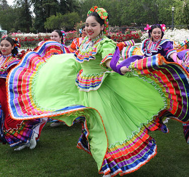 A folklorico group dancing and posing for pictures with the roses at the Municipal Rose Garden.