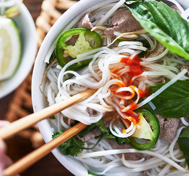 A bowl of Pho garneshed with jalapeno slices, basil, cilantro and lime.