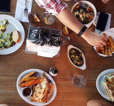 Top view of a table loaded with delicious lunch dishes and friends at Park Station Hashery.