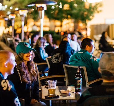 A crowd of Sharks fans have some pre-game drinks on the patio at San Pedro Square Market