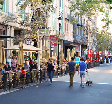 Santana Row strip with people shopping and dining curb side.