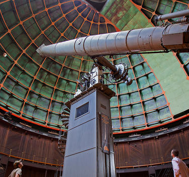 People viewing the giant refractor telescope at Lick Observatory